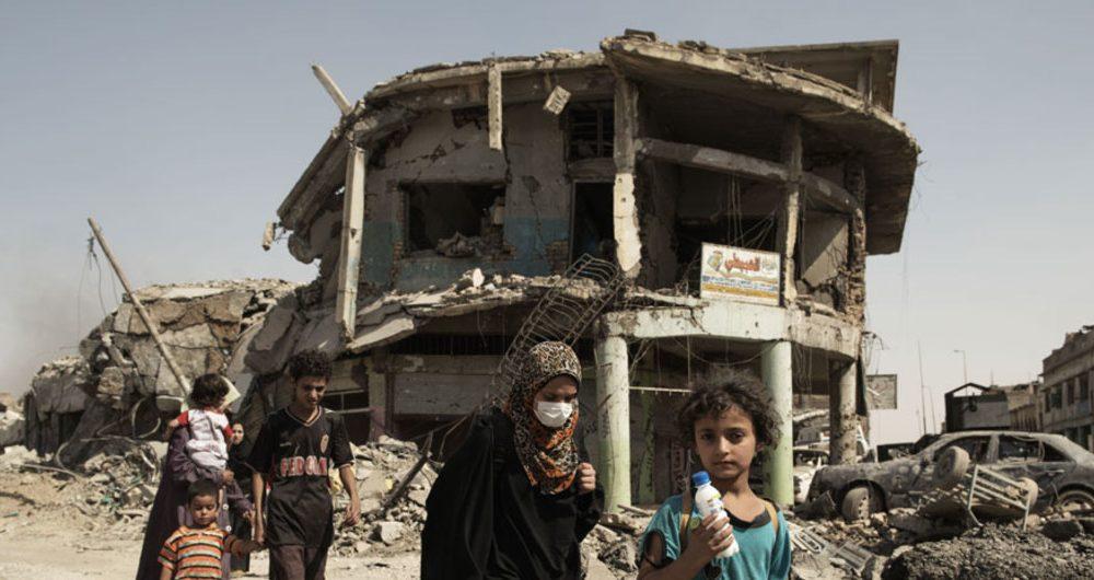 """{""""ar"""":"""""""",""""ru"""":"""""""",""""pt"""":""""Mulheres e crianças andam em meio à destruição em Mossul, no Iraque"""",""""en"""":""""Women and children walk through the debris of buildings and vehicles destroyed during intense fighting as they flee for safe areas in Mosul, Iraq."""",""""fr"""":"""""""
