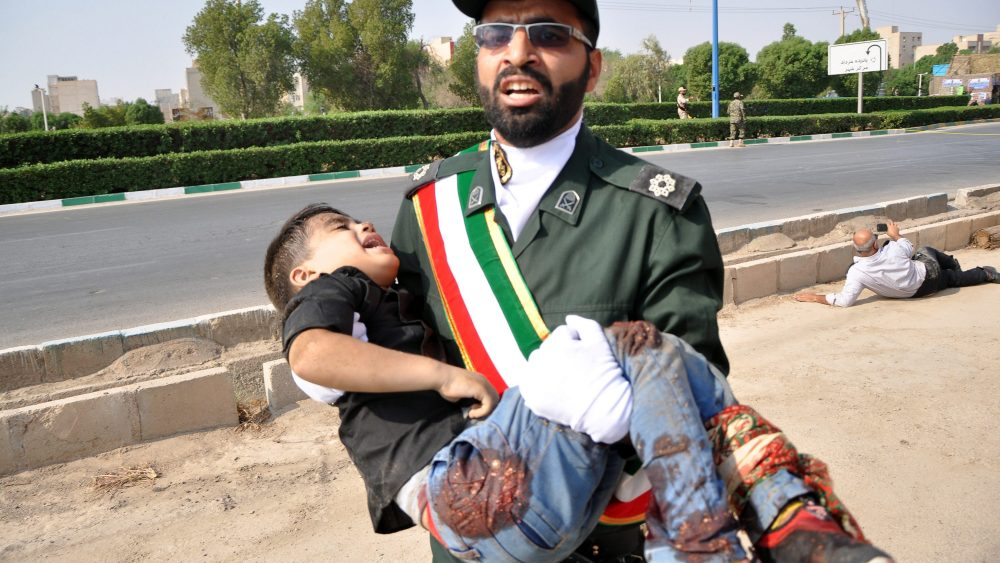 epa07038536 An Iranian soldier carries a child who was injured in a terror attack during a military parade in the city of Ahvaz, southern, Iran, 22 September 2018. Media reported that Gunmen have opened fire during an Iranian military parade in the south-western city of Ahvaz, killing several people.  EPA/BEHRAD GHASEMI