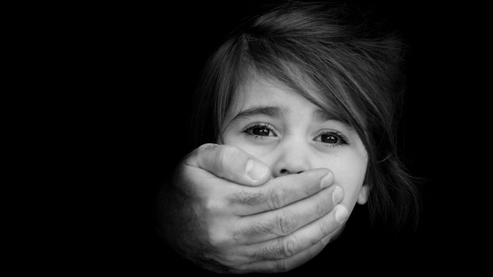 Strong male hands cover little girl face with emotional stress, pain, afraid, call for help, struggle, terrified expression.Concept Photo of abduction, missing, kidnapped,victim, hostage, abused child