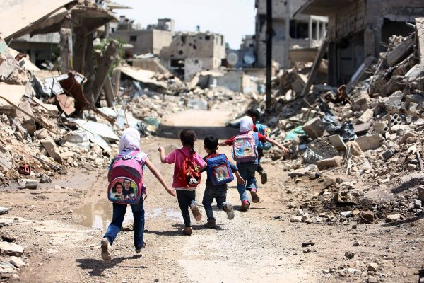 Syrian schoolchildren run past heavily damaged buildings in the rebel-held are of Jobar, on the eastern outskirts of the capital Damascus, on April 30, 2016. / AFP / AMER ALMOHIBANY        (Photo credit should read AMER ALMOHIBANY/AFP/Getty Images)