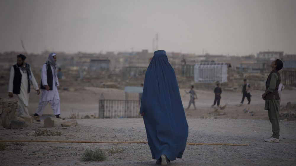 An Afghan woman in a burqa crosses a cemetery where children are flying their kites on a hill overlooking Kabul, Afghanistan, Wednesday, Oct. 16, 2013. During the Eid al-Adha holidays, families often visit the graves of their relatives. (AP Photo/Anja Niedringhaus)