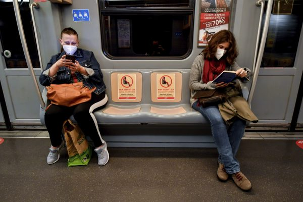 Women read a book and check their smartphones in a subway train as signs reading ' please do not seat here, respect social distances ' are written on seats in Milan, Italy, Monday, April 27, 2020. Italian factories, construction sites and wholesale supply businesses can resume activity as soon as they put safety measures into place aimed at containing contagion with COVID-19. This concession comes with partial easing of national lockdown restrictions announced Sunday night by Italian Premier Giuseppe Conte. (Claudio Furlan/LaPresse via AP)